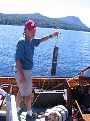 Limnologist-holding-sonde-with-mountains.jpg