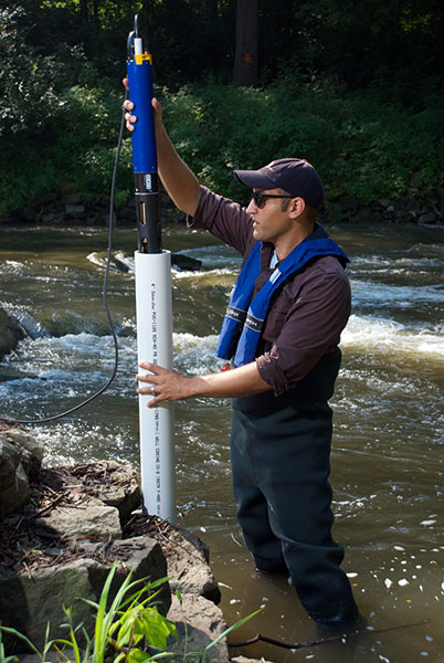 YSI EXO Sonde Being Lowered into a Tube in a Stream